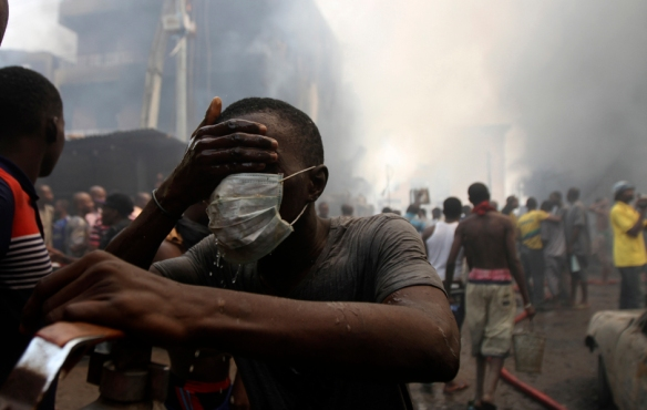 A volunteer cleans his face near the site of a fire, after fireworks stored in a building exploded in Lagos